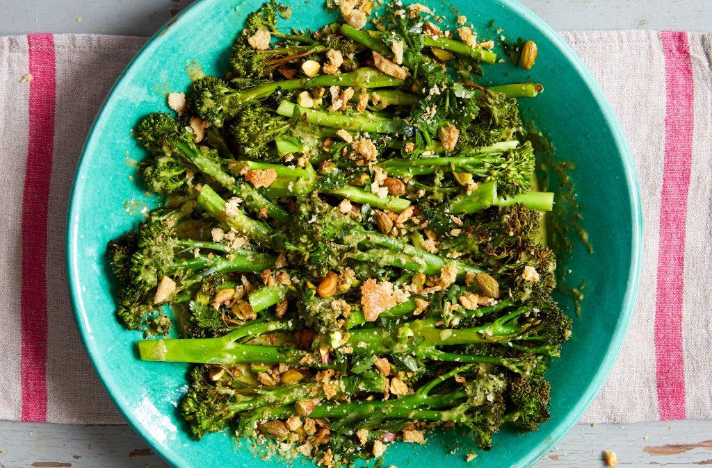 Un plato de brócoli asado y nueces en un teatowel. El brócoli es un vegetal de temporada en el Reino Unido en agosto.